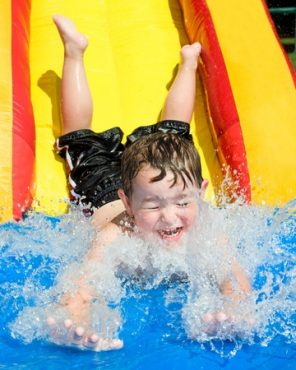 Happy Child Having Fun on a Water Slide at a Summer Party