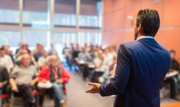 Conference Speaker Talking to a Room of People